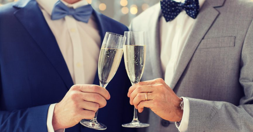 Two men in tuxedos drinking champagne