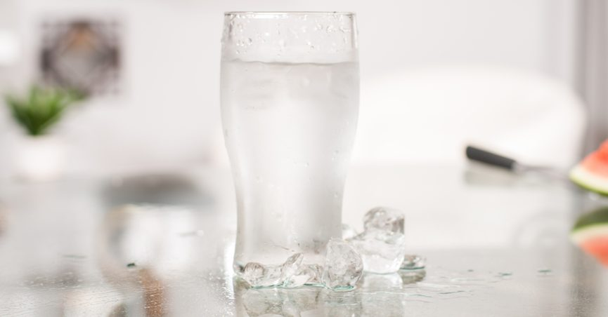 A glass of cold water with ice on a table.