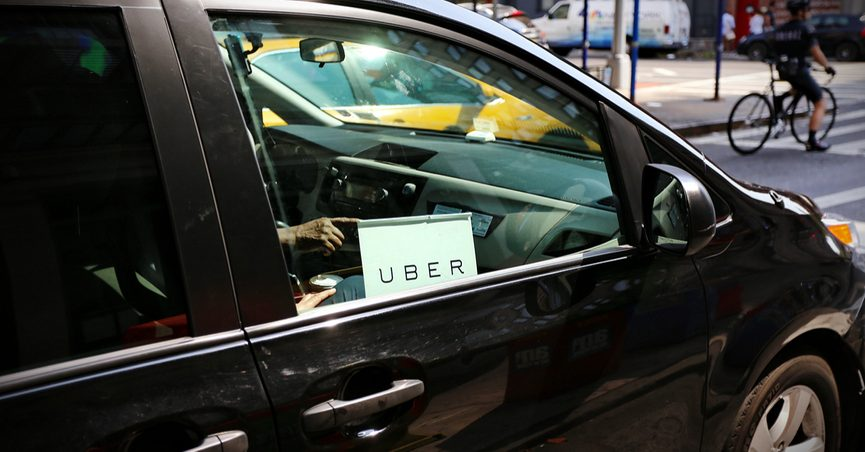 "A black car with an ""Uber"" sign in the passenger side window."