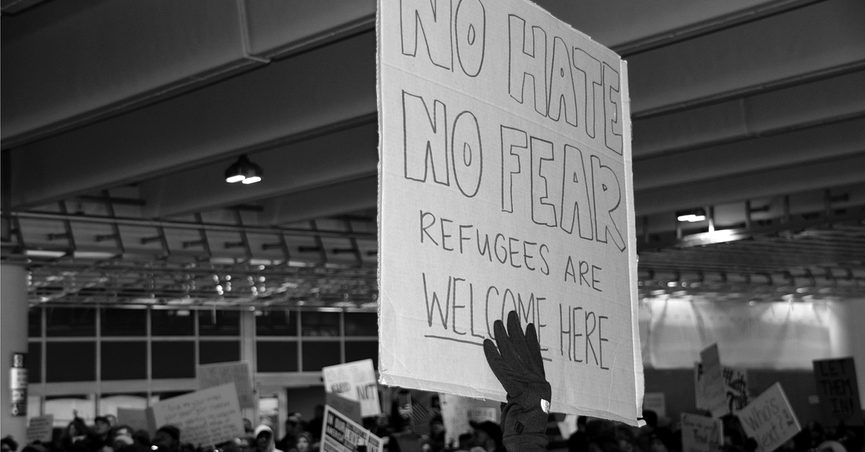 """Protester holding sign that reads: """"No Hate, No Fear, Refugees Are Welcome Here"""""""