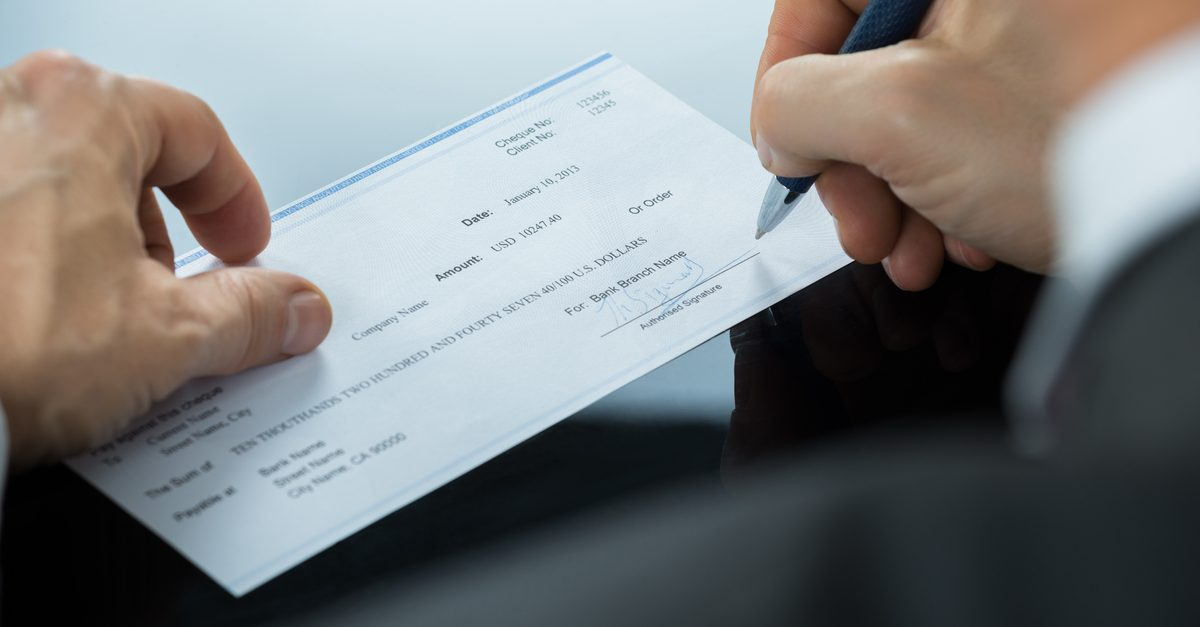 Close-up of someone signing a check.
