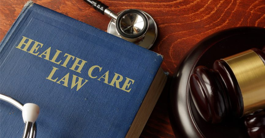 """Book titled """"Health Care Law"""" next to a stethoscope on a table."""