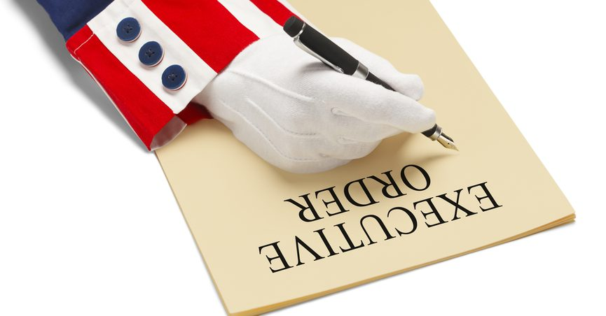 Hand in white glove and red, white, and blue cuff signing a piece of paper that says: EXECUTIVE ORDER.