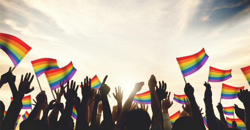 Silhouettes of a crowd of people waving rainbow flags.