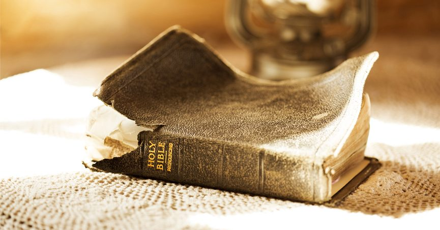 Old, torn-up Bible illuminated by a sunbeam