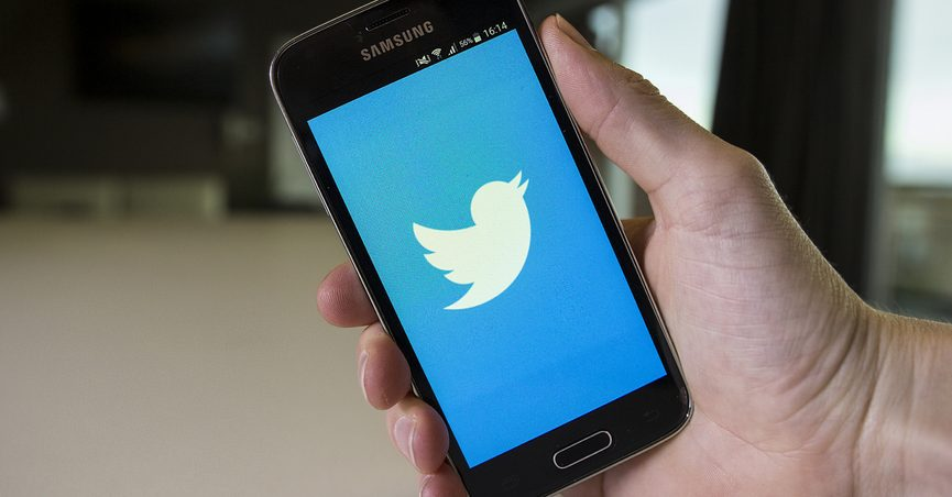 Hand holding smartphone that is displaying a large Twitter logo