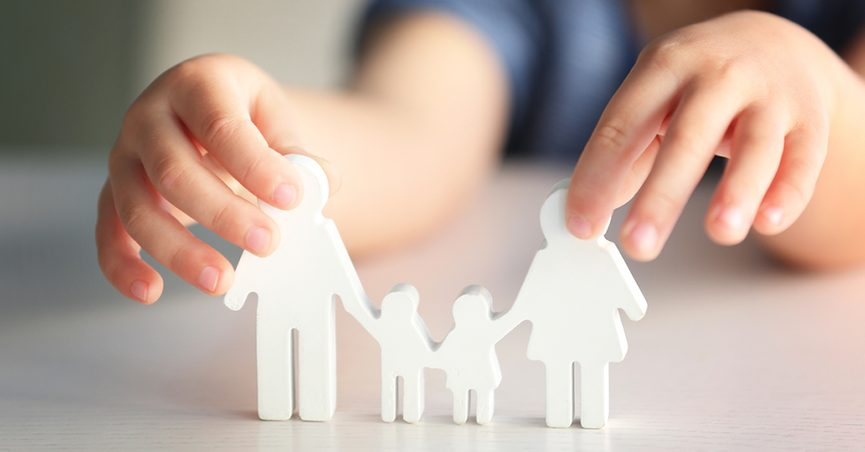 Child holding a paper cutout of a family.