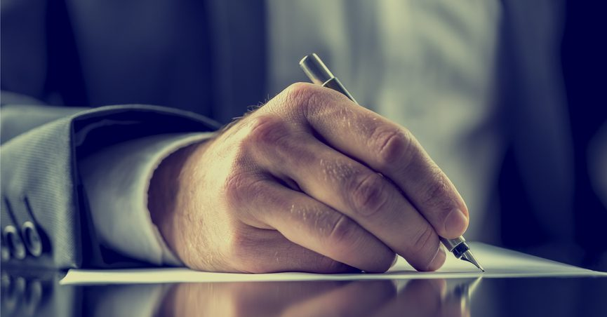 Close-up of man hand writing a letter