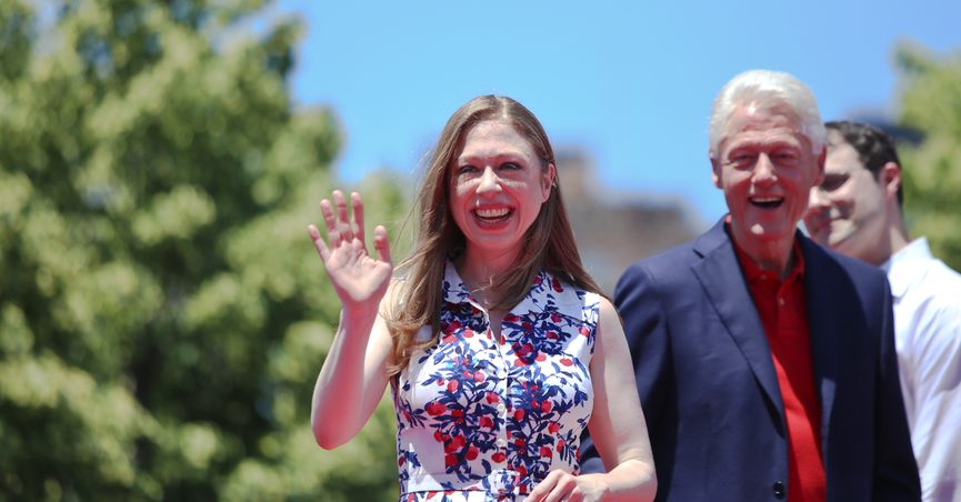 Chelsea Clinton waving at the camera with her father, Bill Clinton, in the background