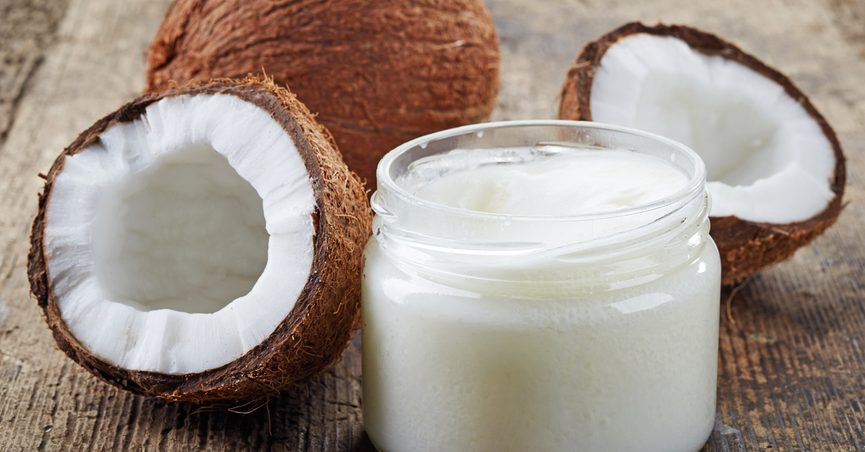 Coconuts next to a jar of coconut oil.