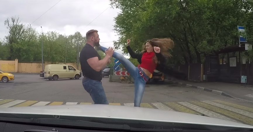 Still from a video showing a woman delivering a roundhouse kick to a man in front of a car