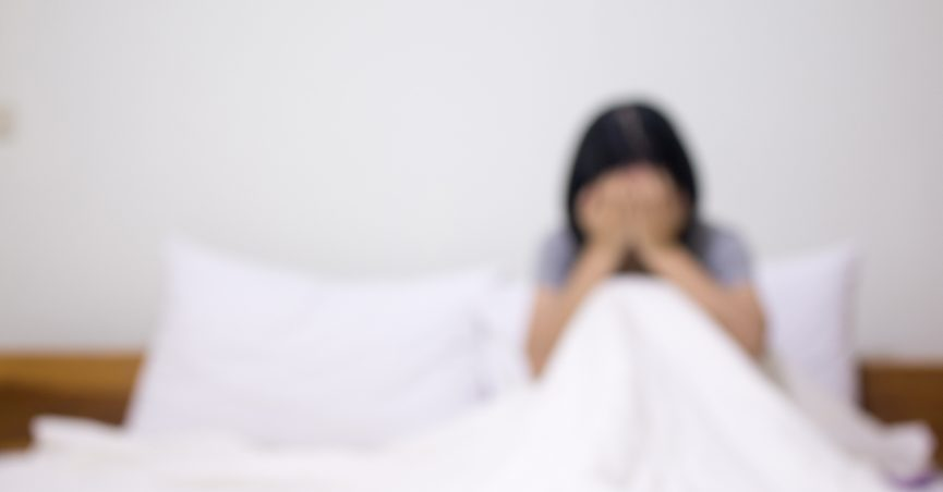 Blurred photograph of woman crying alone in bed.