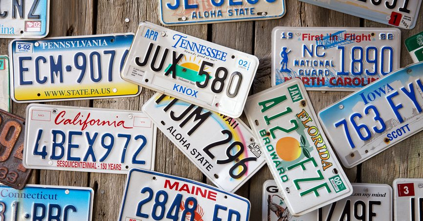 License plates from various U.S. states scattered across a flat wooden surface