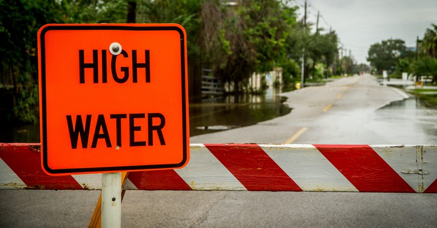 """""""High Water"""" sign in front of water coming over a road in Kemah during Hurricane Harvey"""