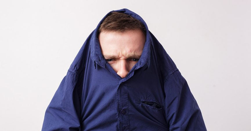 Man with head stuck in blue collared shirt