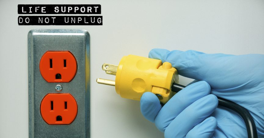 """A plug being pulled from an outlet labeled: """"Life Support: Do Not Unplug"""""""