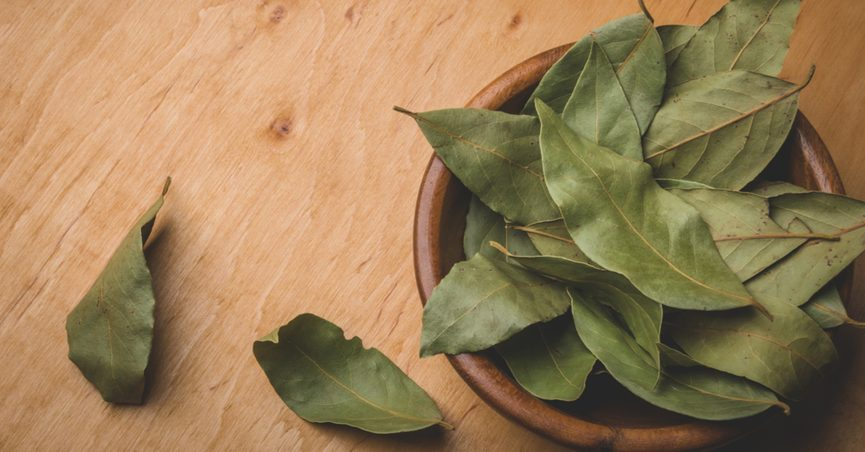Bowl of bay leaves on wooden surface
