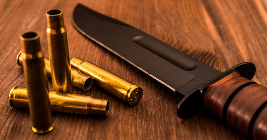 Empty shells, a rifle, and combat knife on a wooden table