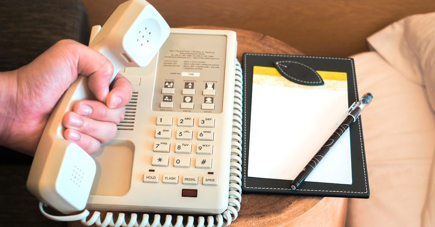 Person holding hotel phone receiver