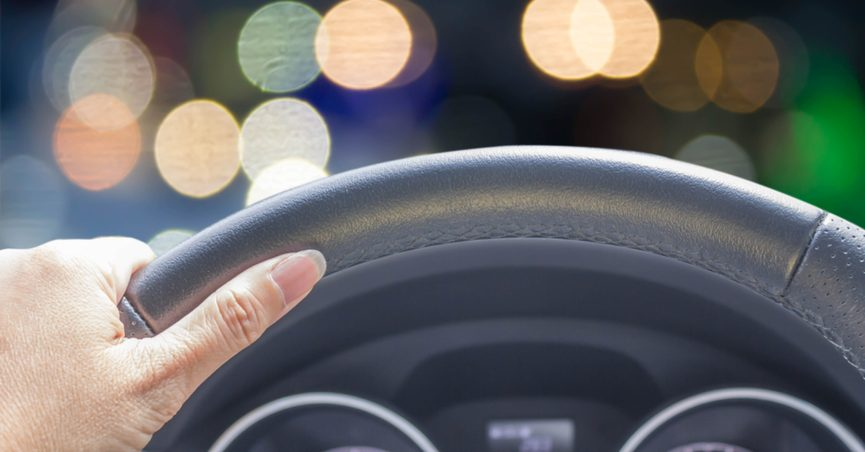 Woman's hand holding a steering wheel with bokeh lights in the background