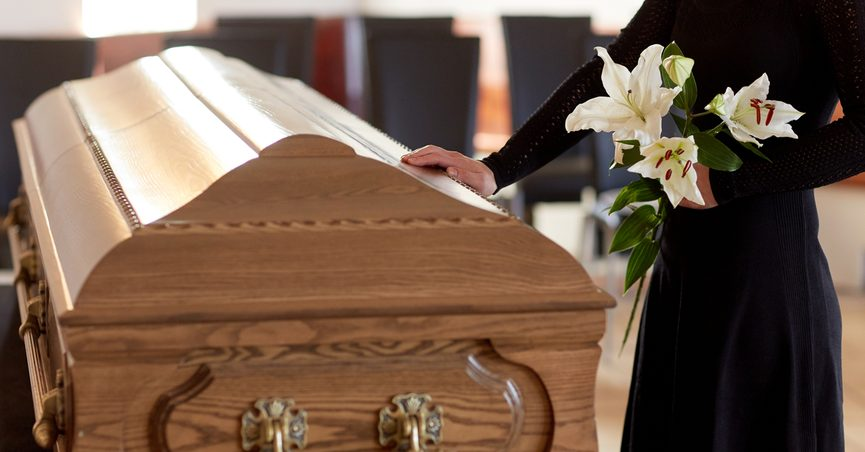 woman with white lily flowers and coffin at funeral in church