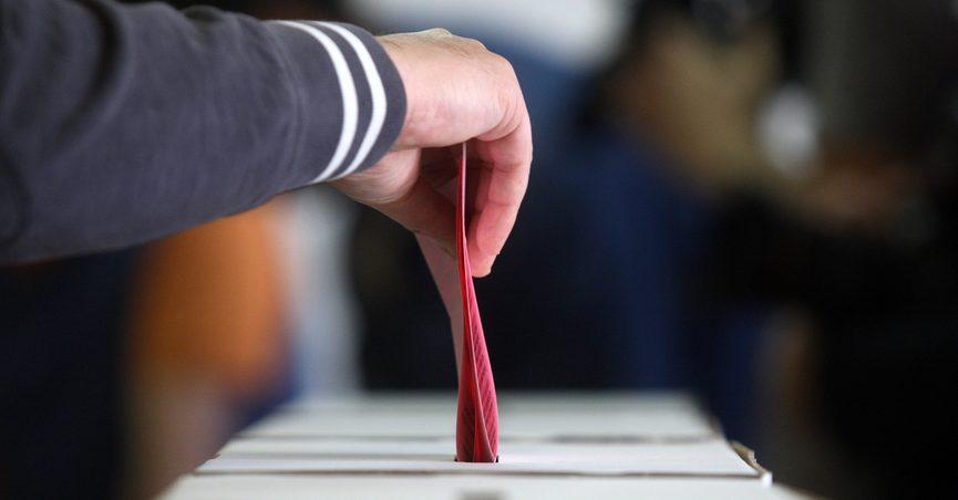 Older man voting at elections, hand putting ballot paper in ballot box.