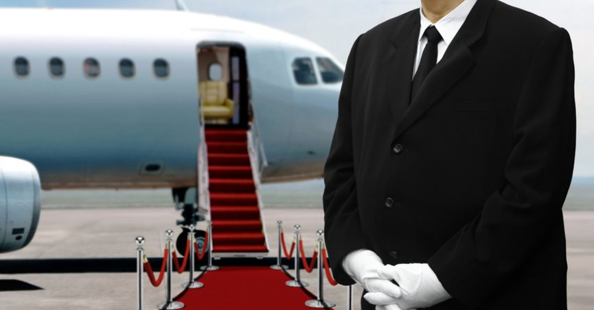 Man in suit waiting in front of a private jet