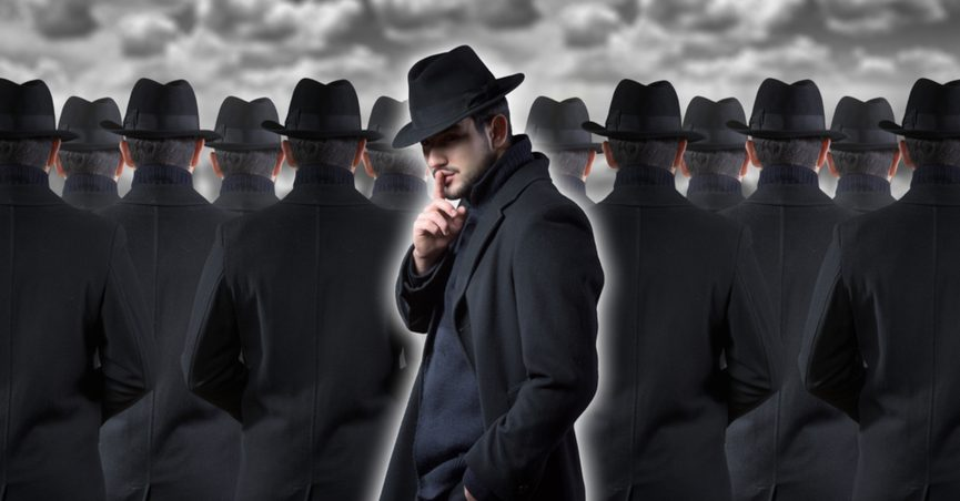 Mysterious man making a silence gesture while standing out from the crowd