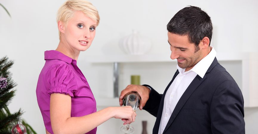 Man pouring woman's drink as she looks at the camera