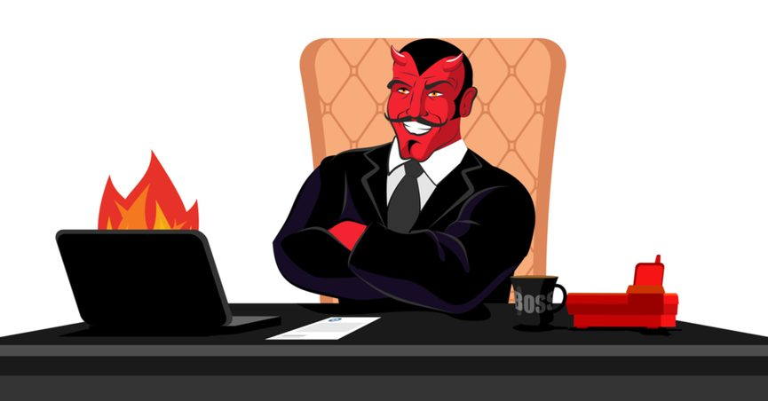 Artistic representation of Satan in a suit sitting at a desk in front of a burning laptop.