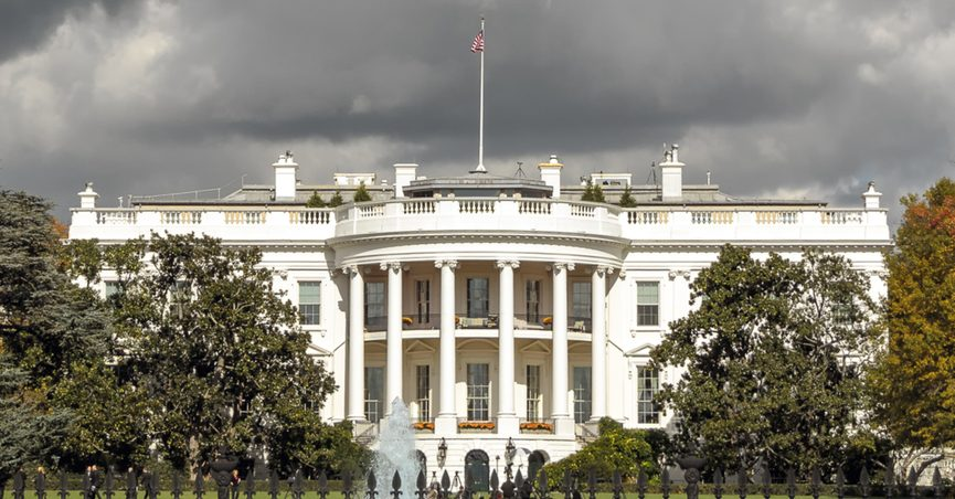 Exterior shot of White House in Washington, D.C., under a cloudy sky.