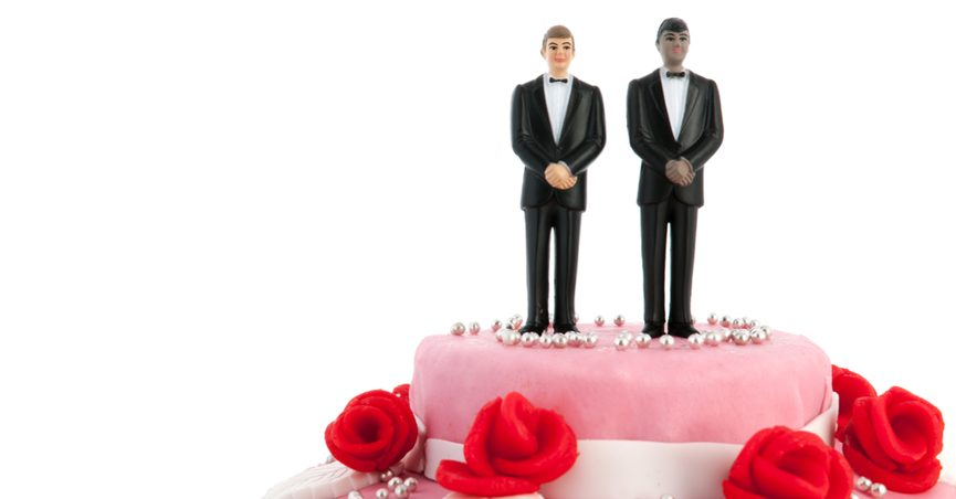Wedding cake with figurines of two men in suits on top.