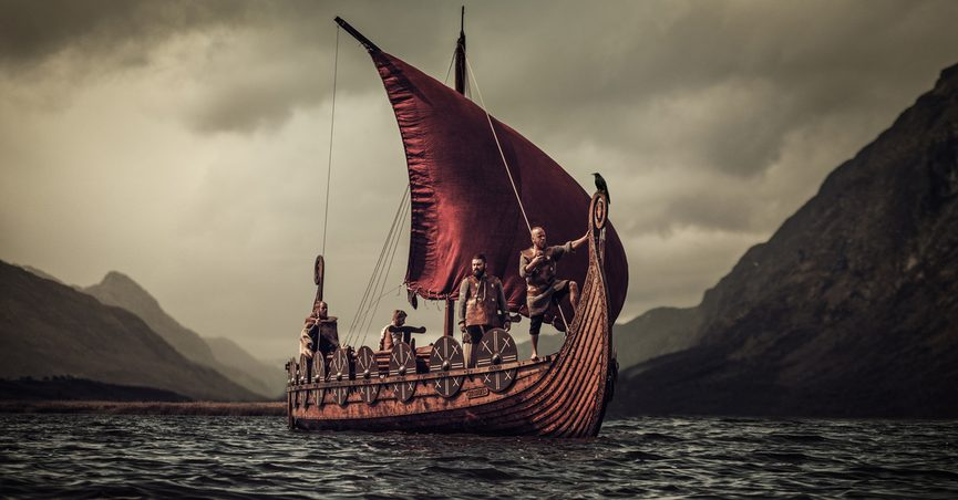 A group of Vikings floating on the sea on Drakkar with mountains on the background.
