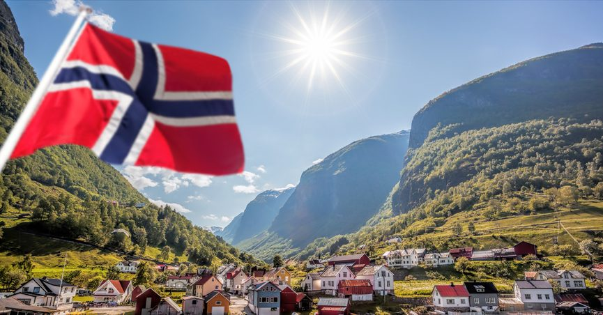 View of small fishing town with Norwegian Flag in foreground