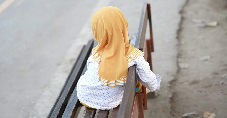Young girl in hijab sitting on a bench