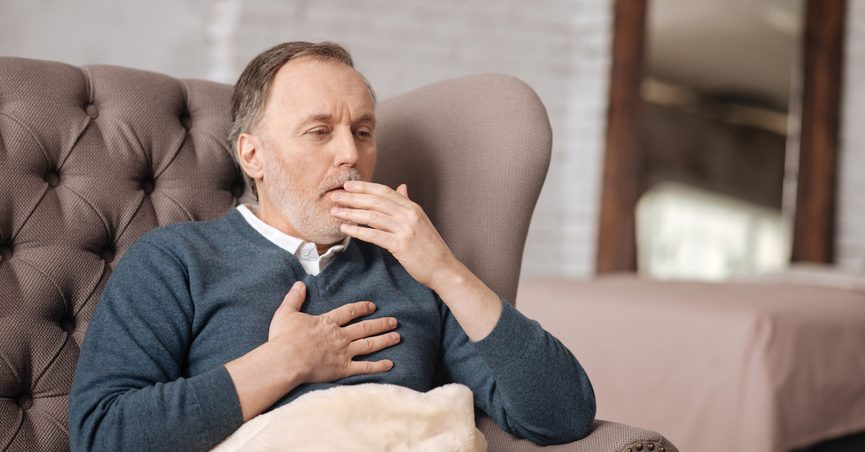Man coughing and holding chest