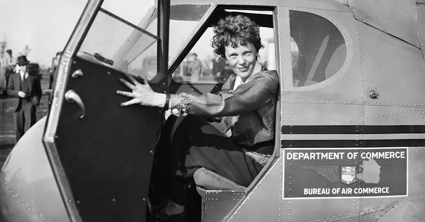 Amelia Earhart smiling from her cockpit.