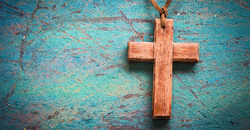 A wooden cross hanging on a blue wall.