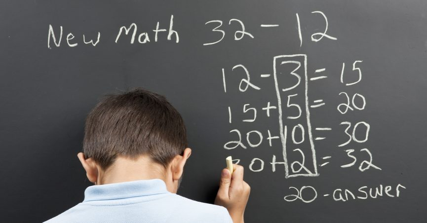 Student solving a math problem using Common Core techniques on a blackboard.