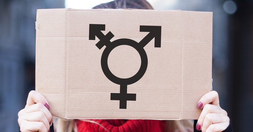 Hands holding a sign with a transgender logo.