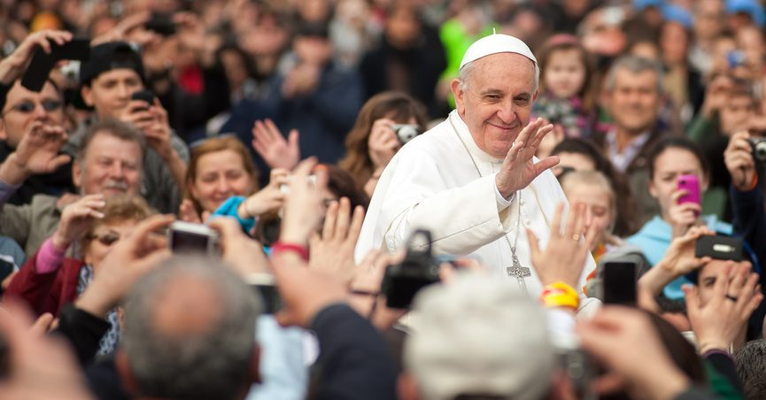 Smiling Pope Francis surrounded by a crowd.