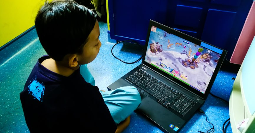 A child sitting on a floor watching a YouTube channel on a laptop.