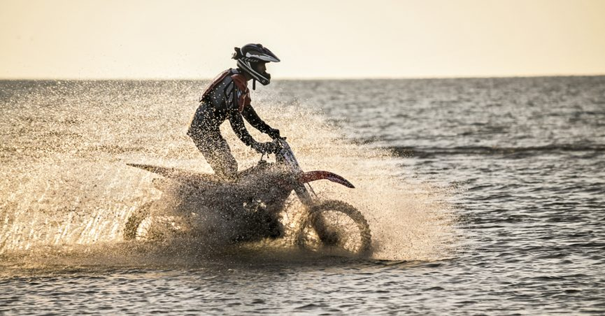 A rider on a cross-country motorcycle rides by the sea and raises a spray of water.
