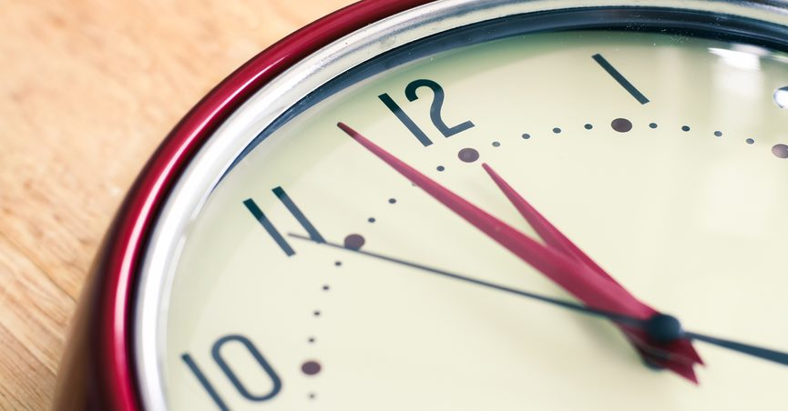 Analog clock face showing two minutes to midnight (or noon.)