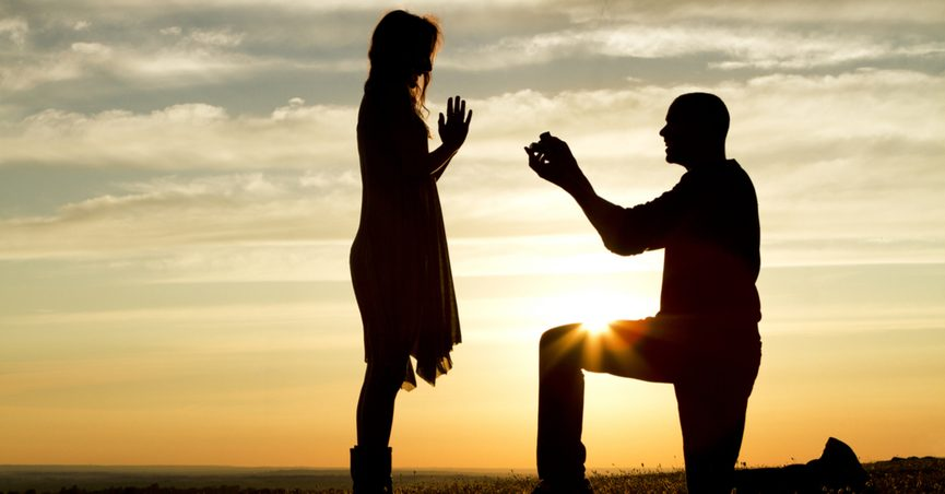 Silhouette of a man kneeling to propose to a woman.