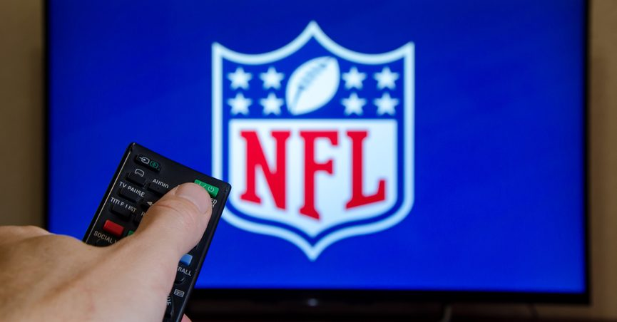 Hand holding remote in front of television screen displaying the NFL logo.
