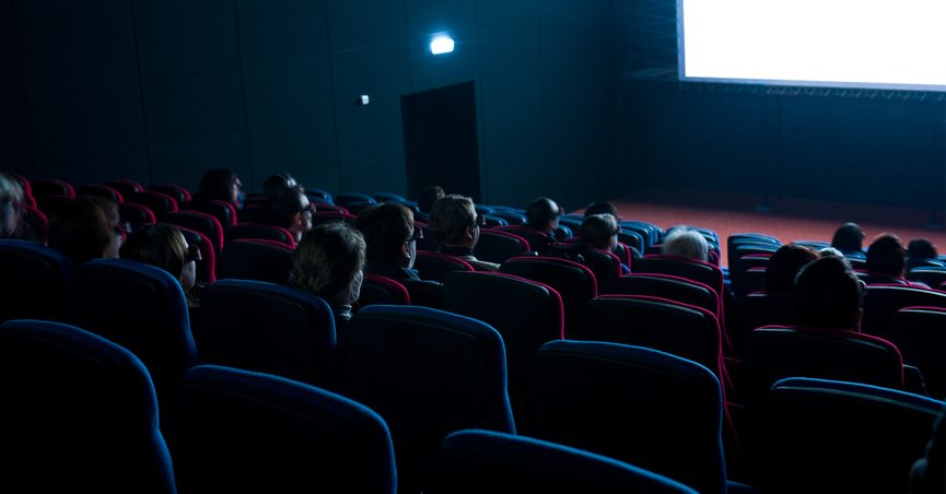 People watching a film in a darkened movie theater.