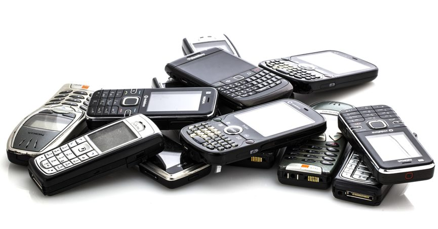 A pile of old mobile phones against a white background.