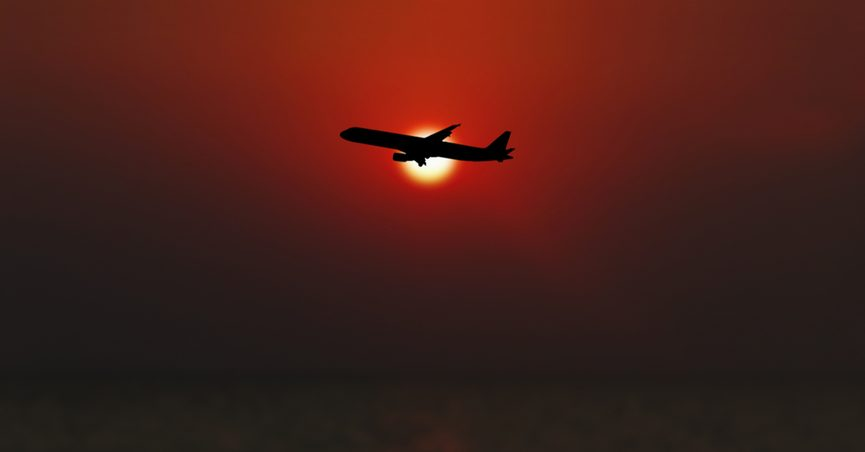 Airplane flying with sun in background.