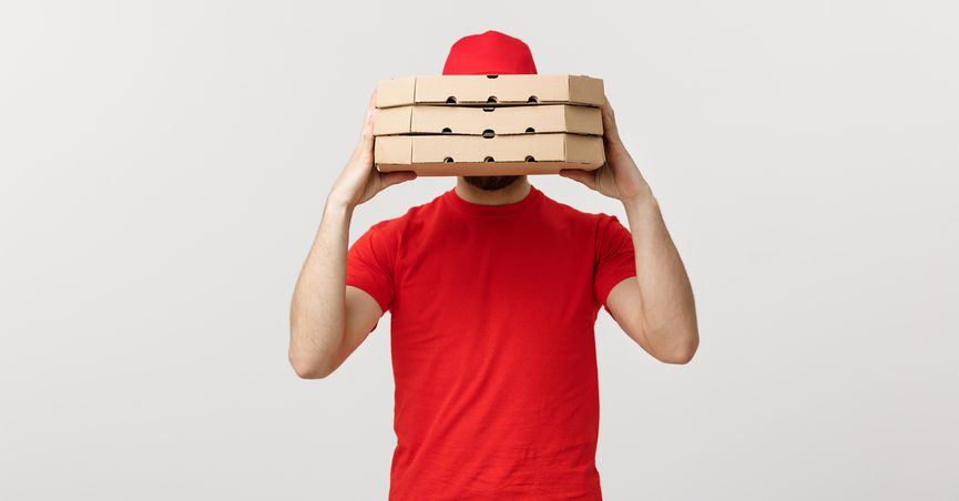 PIzza delivery man hidden behind boxes.